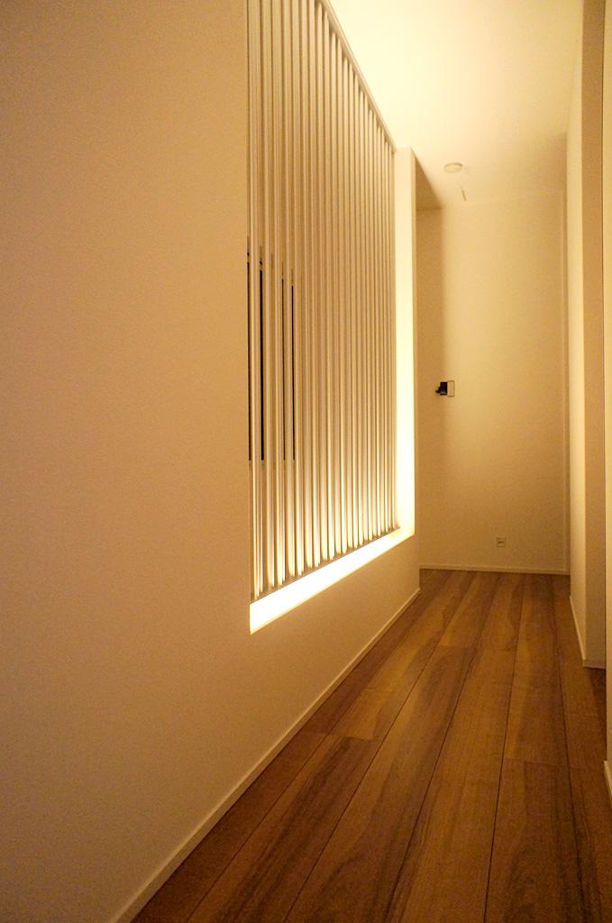 スチール柱でつくられた壁が印象的な2階ホール。そのスチール柱が足元の光を天井まで届ける。