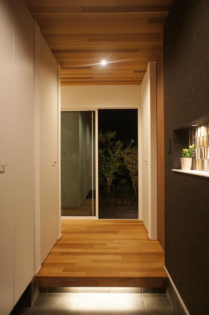 床タイルを照らす間接照明が印象的な玄関。 奥に広がる空間への期待が高まる。