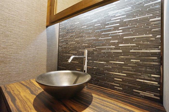 トイレ内に設けた手洗。鏡背面は硬質金属を組み合わせたモザイクタイルで仕上げ、モダンなアクセント壁を創り出している。