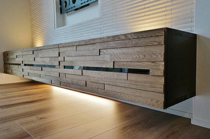 TV下収納の扉は、木片をブロック状に組み合わせその凹凸と木目を愉しむ。中央のアクリルスリットはリモコンの光を透過する。造形美と機能双方に配慮が行き届いている。
