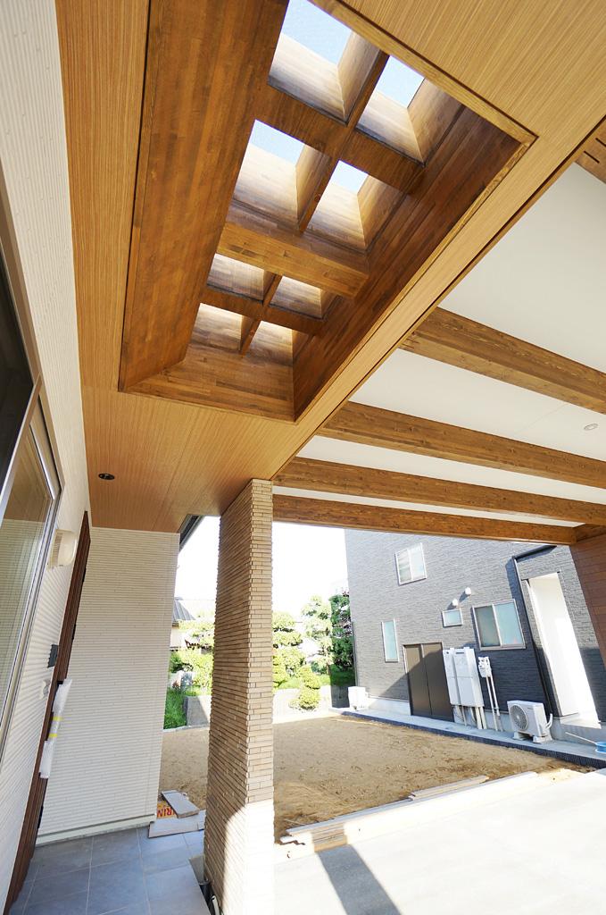 玄関アプローチに設けたトップライトから自然光が降りそそぐ。耐候性の高いポリカーボネイトは光を集めるプリズムタイプを採用している。