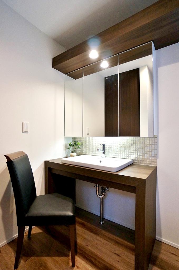 洗面化粧台は下がオープンタイプとなっており、ドレッサーとしても使用できる。間接照明にきらめくガラスモザイクが印象的。