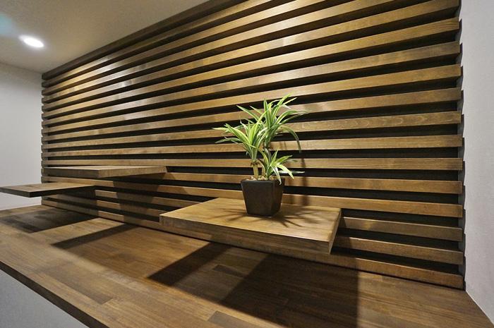 リビングメインの飾り棚は、差し込み式の可動棚を使い自由なレイアウトが可能。 背面の横格子がその機能と共に空間をよりモダンに演出しオブジェを引き立てる。