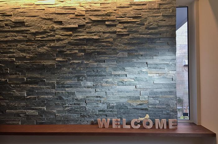多くの来訪者を迎える玄関ホールに配した、天然石の壁面アクセント。自然光と間接照明で、照らされた壁面の陰影は、昼と夜に違った顔を持つ。
