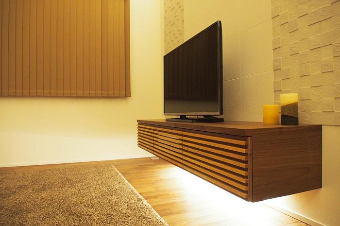 リビングのTVボードは、 ウォ-ルナットの質感と 壁面のエコカラット、 間接照明が相まって、 独特の存在感を醸し出す。