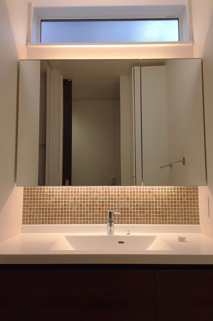 壁面一杯に使った洗面スペース。細かな造り込み一つ一つが、ホテルライクな雰囲気を演出。背面にあるトール型収納で、洗面所内の収納を担う。