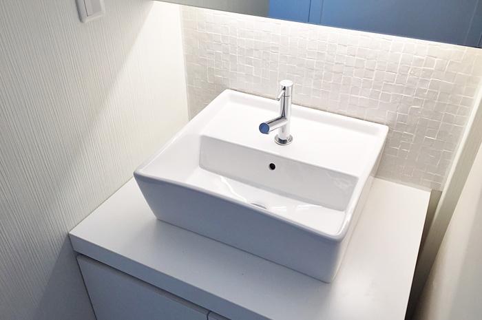 トイレ脇に配置された手洗い器。ホワイトの部材やタイルが、清潔感をもたせる。