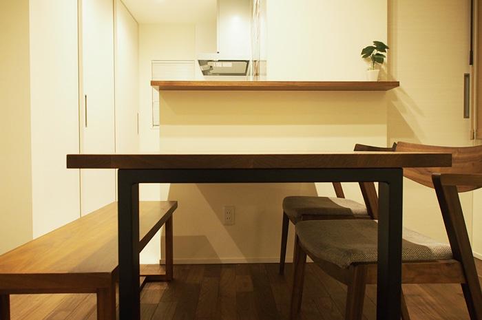 周辺の材質に合わせた、オーダーメイドのダイニングテーブル。キッチンとは、横につながり、スムーズな家事動線の中にある。