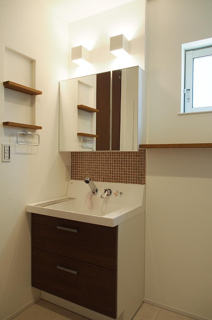 既製の洗面カウンターを利用した造作洗面台。タイルや照明がオリジナリティーを演出。