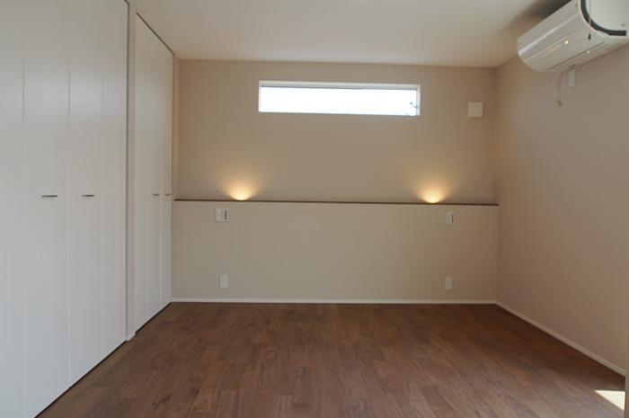 ベッドヘッドには小物を置けるライニングカウンターと、壁面をやわらかく照らす照明を配置。