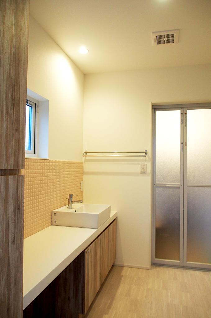 造作で作った洗面台は家族でならんで身支度をできるように幅をもたせました。 奥にはサンルームが配置されております。