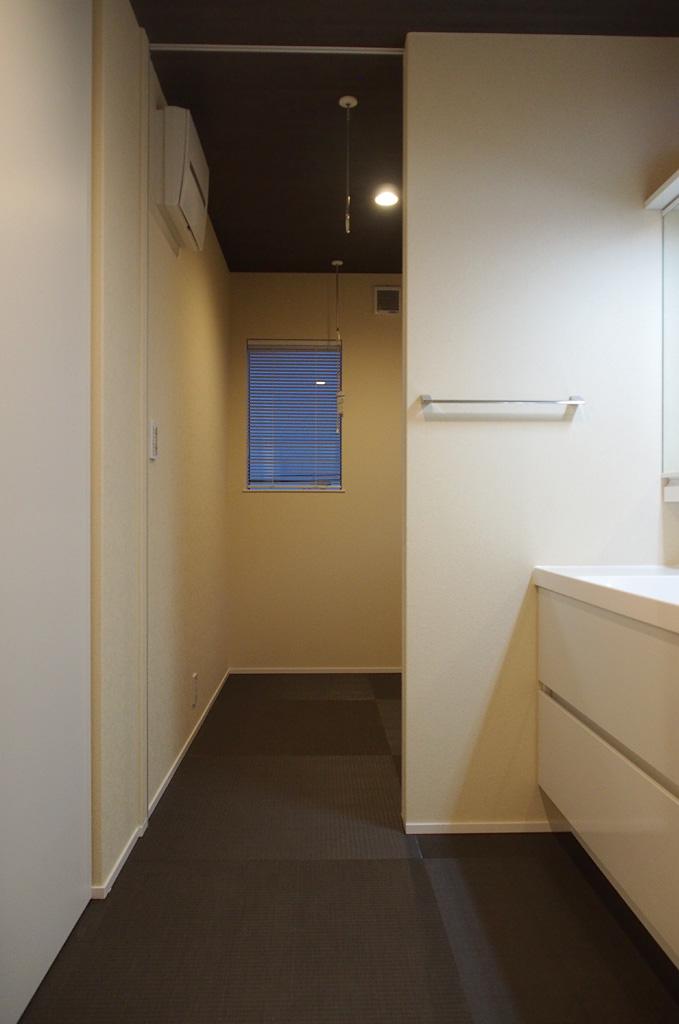 洗面脱衣室の奥には日当たりのいいランドリースペースを配置。床は濃いめのタタミで、床に座って服をたたんだり、アイロン掛けができる。