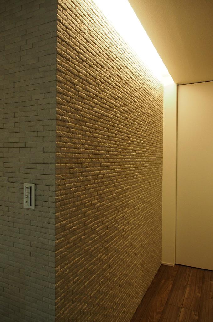 玄関ホールにある壁面タイルとそれを照らす間接照明が来客をやさしく迎え入れる。