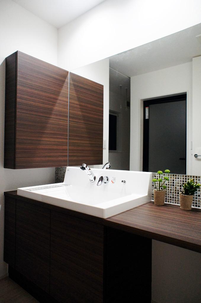 メイクスペースを兼ねた洗面は1.5m幅の大きな鏡が印象的。邪魔にならない位置に収納BOXを製作。