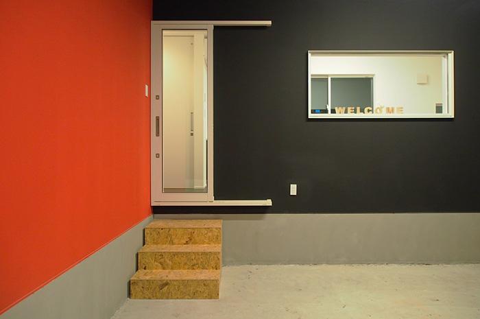 ガレージと室内を繋ぐアプローチ。ステップが色彩のアクセントに。