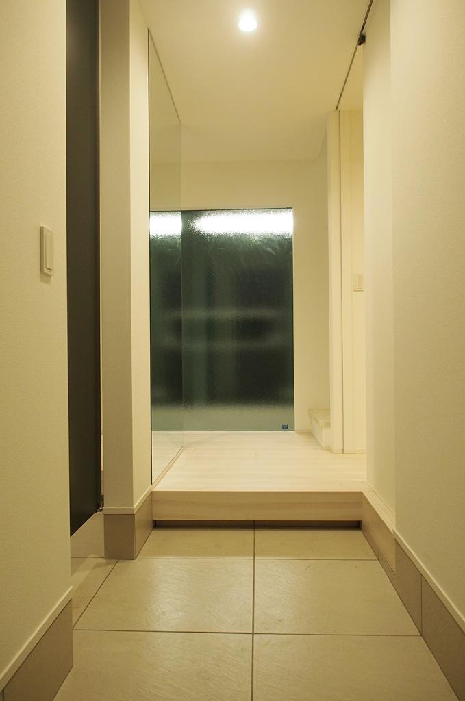玄関は大きなFIXサッシによる採光と色彩に伴って、明るく清潔な空間となった。玄関まわりにある収納もたっぷりと確保。