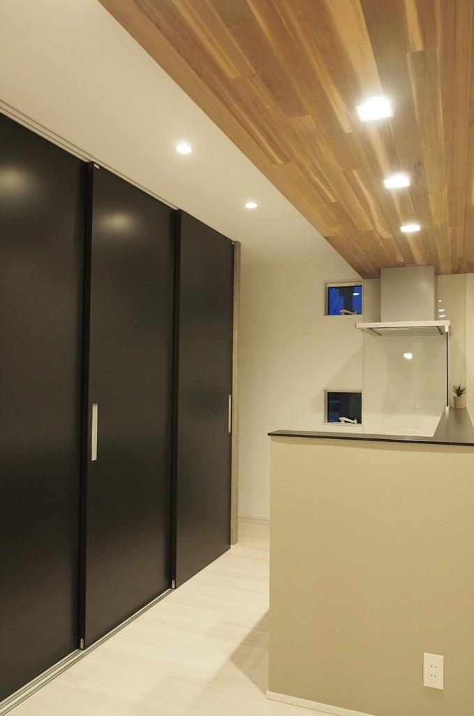 キッチン収納には、来客時にすぐに目隠し対応できる引戸タイプを採用。キッチン上にデザインした木目の下がり天井が、キッチン一帯の雰囲気をを引き立てる。