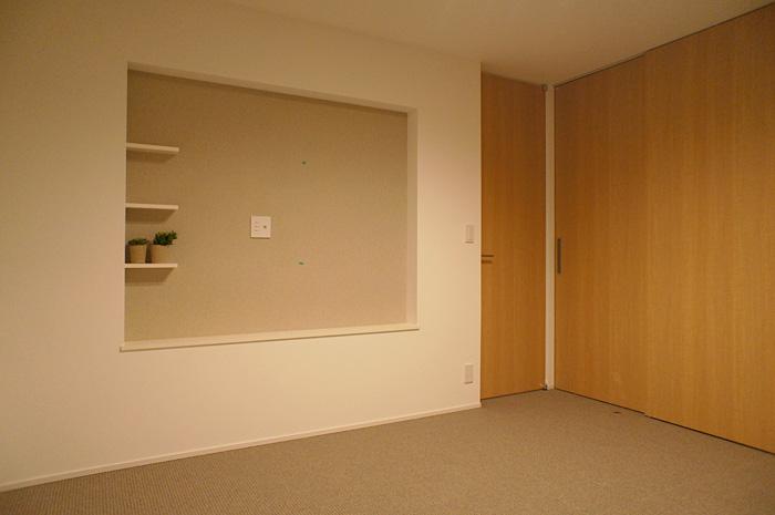 寝室の壁掛けTVスペースは壁紙にアクセント色を入れて表情をつけた。