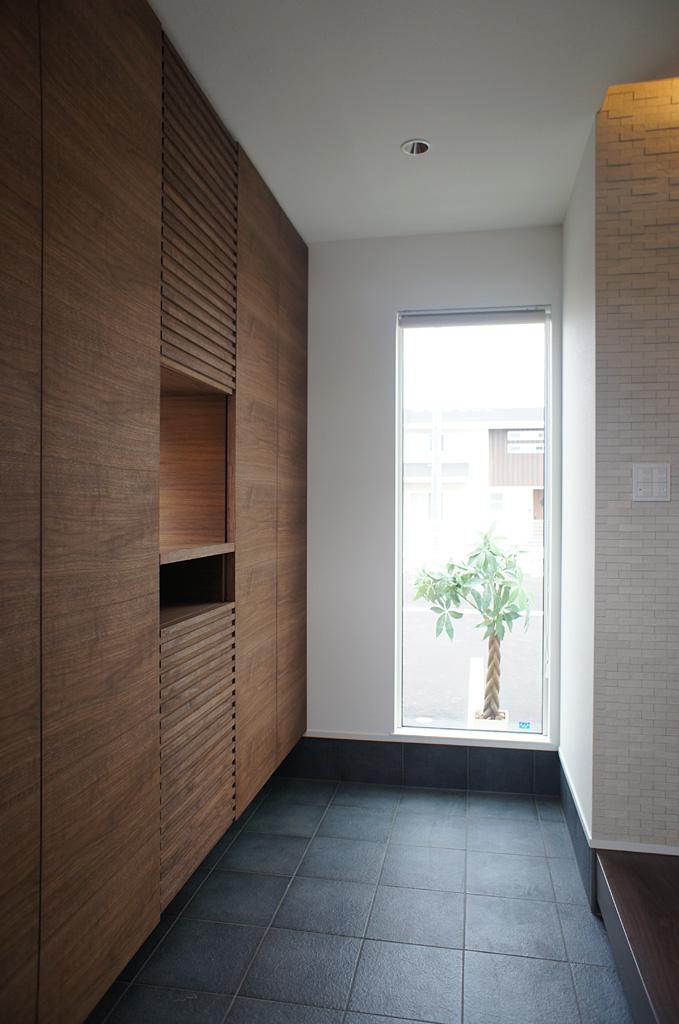 大型の玄関収納を造作し、収納量を確保。奥に設けた大きな開口が玄関に「広がり」と「抜け」を生み出す。
