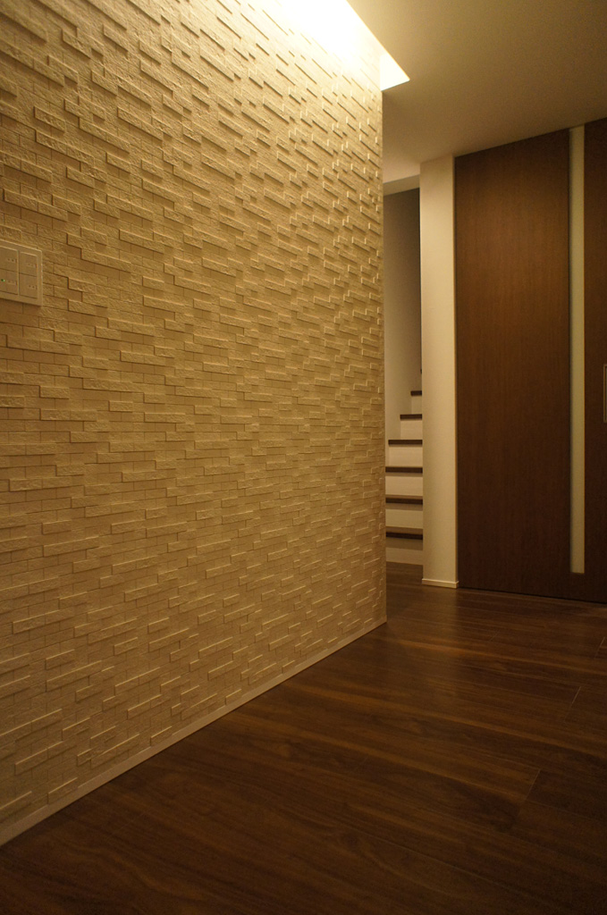 玄関のエコカラットと照明が豊かな空間をつくる。