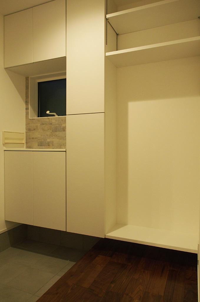 既成品の玄関収納に棚やタイルを組み合わせ一体化することでコストをおさえた造作玄関収納。