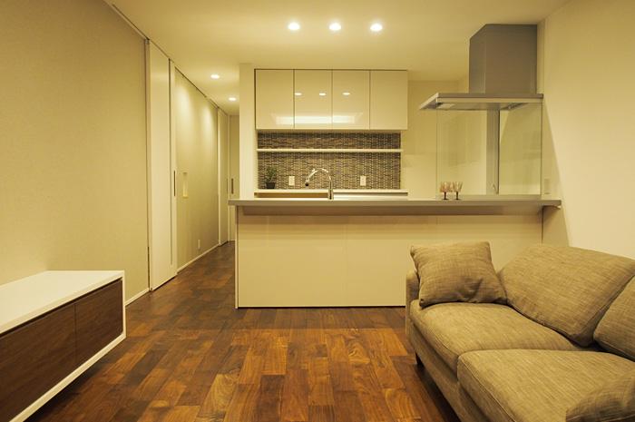 キッチンをメインに配置したLDK。白のキッチンやTV台と濃いめのウォールナット無垢材のメリハリが空間を引き締める。