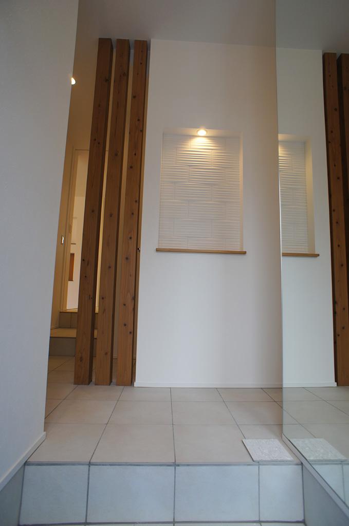 玄関ホールには、あらわしの柱とニッチ、壁面鏡、タイル床を取り入れた。