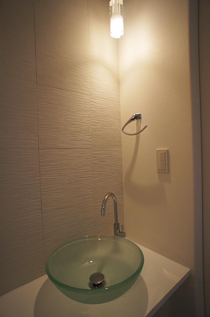 玄関ホール付近に設置された手洗い器。帰宅時に手洗いがすぐに出来る。壁面には、調湿効果と消臭効果を備えた、おなじみのエコカラットを採用。