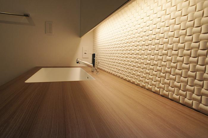 洗面台の扉と同色のカウンターもタイルを照らす間接照明と相まって、落ち着いた雰囲気をつくりだす。