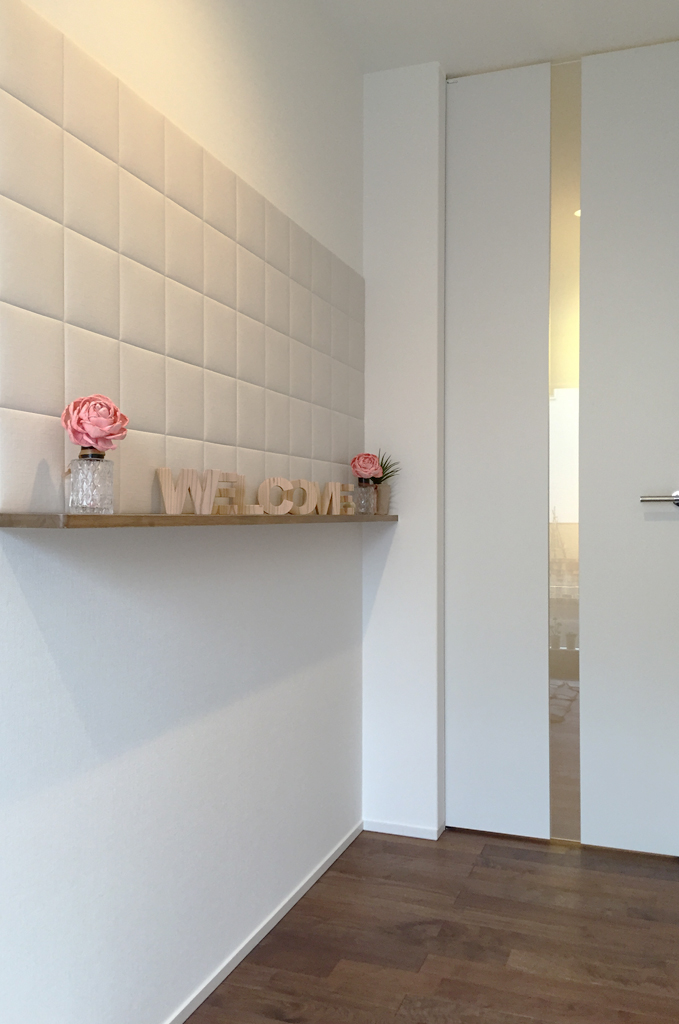 玄関ホールデザインは、エコカラットとニッチを組み合わせた壁面に、ウォ-ルナットの無垢床材、フルハイトドアが相まって、やさしく上質な雰囲気を演出しました。