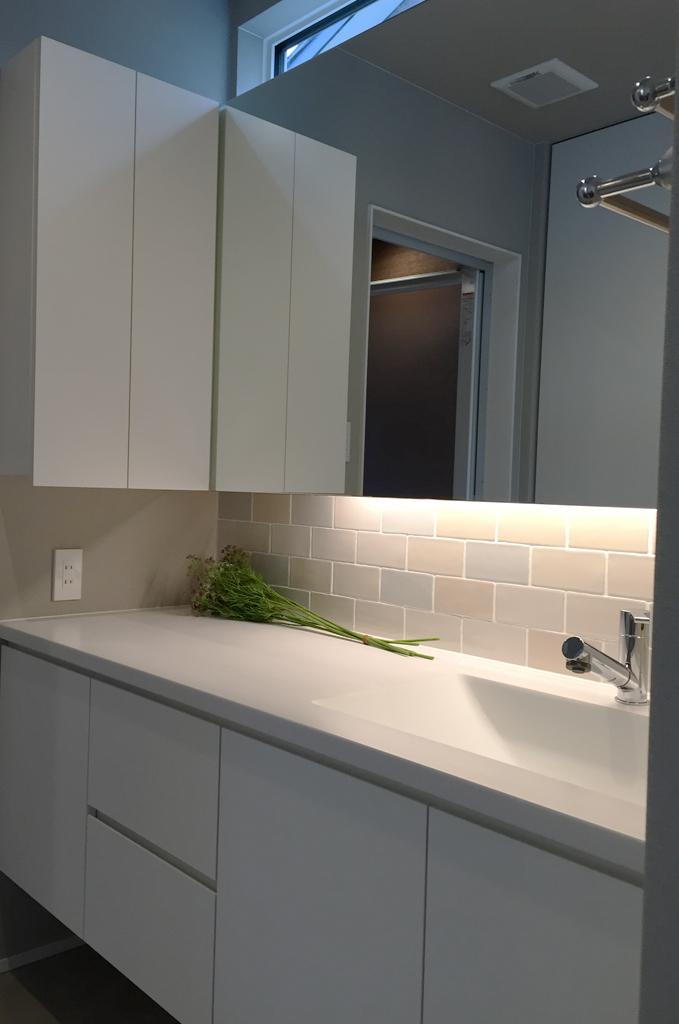 ホワイト色でまとめたで造作洗面台。間接照明やタイルの配色もディテールイズム。