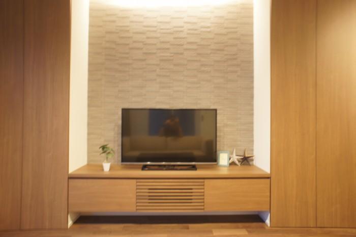 ウォールナットの床材に合わせたTV台と収納建具を造作。 TV背面にはアクセントにグレー色のエコカラットを配置。