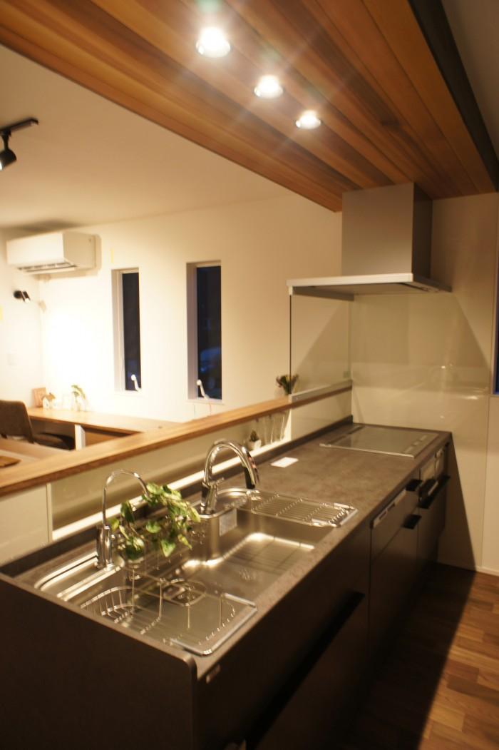 キッチン天板はLIXILの高級セラミック天板を採用。 ブラックのキッチン上の天井にはアクセントにレッドシダーを。
