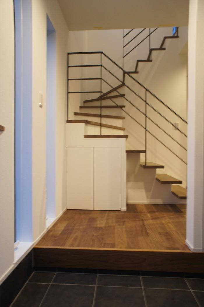 玄関を開けて圧迫感を無くすためにアイアンの手すりで開放的な階段を演出。 配色はウォールナットの床にブラックのアイアンでシックでモダンな雰囲気に。 階段下のデッドスペースも収納として有効活用。存在感を無くすためにホワイトの扉を採用。