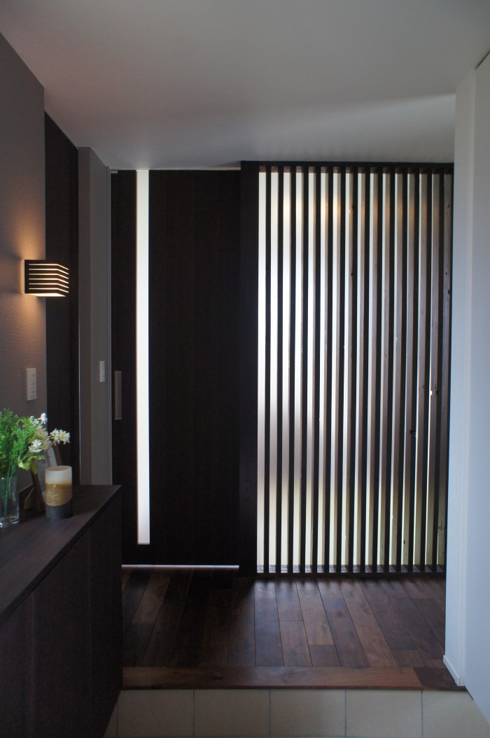 玄関に一歩踏み入ると、格子壁面が存在する。格子は空間を閉じすぎず、開きすぎず、プライバシーを適度にコントロールする