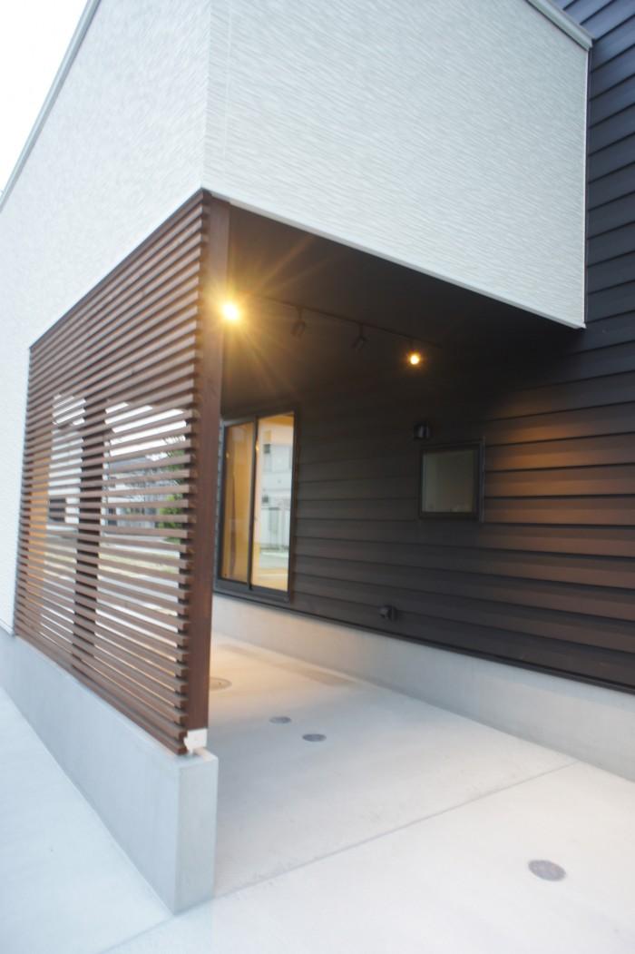ブラックの金属の外観をベースにインナーガレージ部分はホワイトの外壁に貼り分け。正面には木製のルーバーとレッドシダーで表情を変えている。