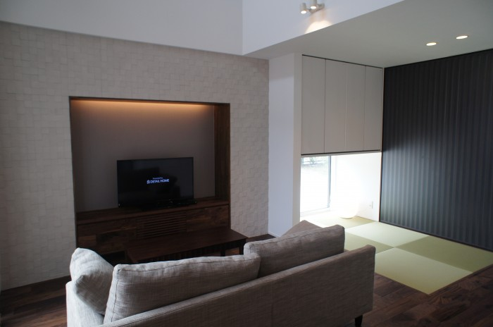 壁面一面白のタイル・白い内装に無垢床のウォールナットと造作家具が映えるシックな空間を演出。
