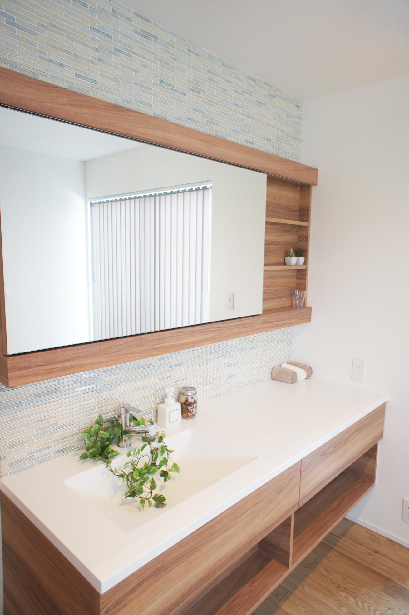 製作の洗面化粧台を明るい床の色に合わせてオークの色味とモザイクタイルで明るさを表現。 アイロン掛けもできるようにワイドは広め。鏡がスライドして裏には収納スペースが。