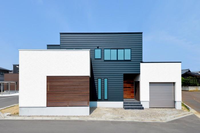 ブラックの金属の外観をベースにインナーガレージ部分はホワイトの外壁に貼り分け。 正面には木製のルーバーとレッドシダーで表情を変えている。
