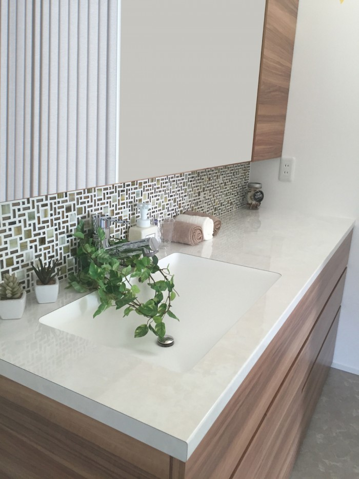 アイロン掛けなどの作業台も兼ねた幅広の洗面化粧台を製作。 鏡下にはガラスモザイクタイルを採用。