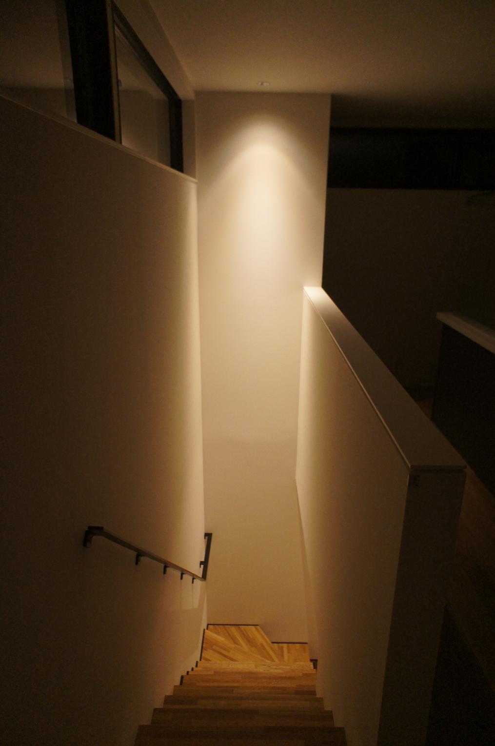 ユニバーサルダウンライトで印象的な階段吹き抜け空間。