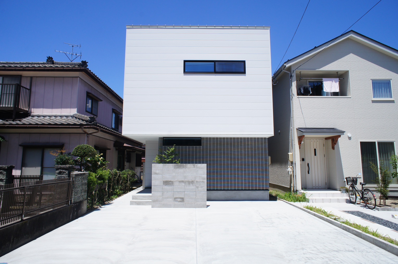 白と黒のコントラストが効いたファサード。 外壁の目地とサッシをあわせることで生まれる美しい体裁。