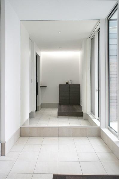 大開口と大型ミラーに囲まれた玄関ホールは畳数以上の広がりを生む