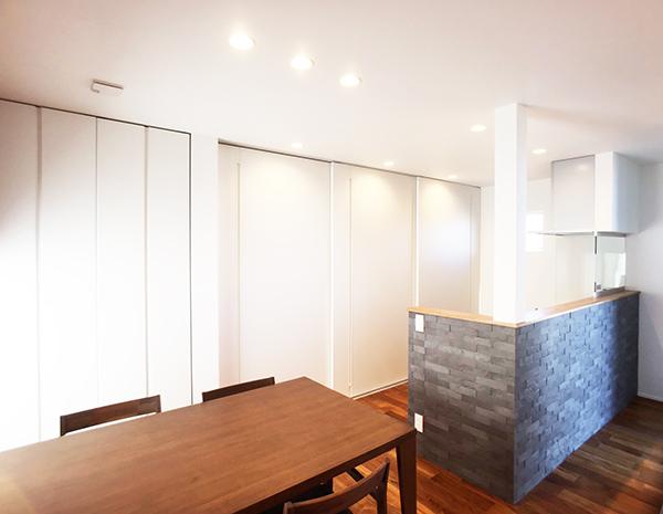 エコカラットをキッチンを囲むように貼り、カラーアクセントとした。手元が隠れたキッチンは使い勝手を重視した。 キッチン背面収納は全て建具で隠せる。ホワイトで統一した壁面がスッキリとした空間を際立たせる。
