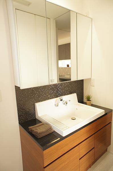 間接照明できらきら輝くガラスモザイクタイルが美しい洗面台。